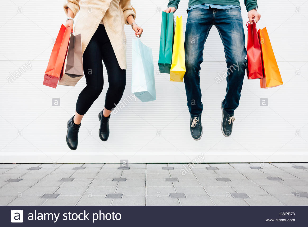 Closeup of woman and man jumping with shopping bags - Stock Image