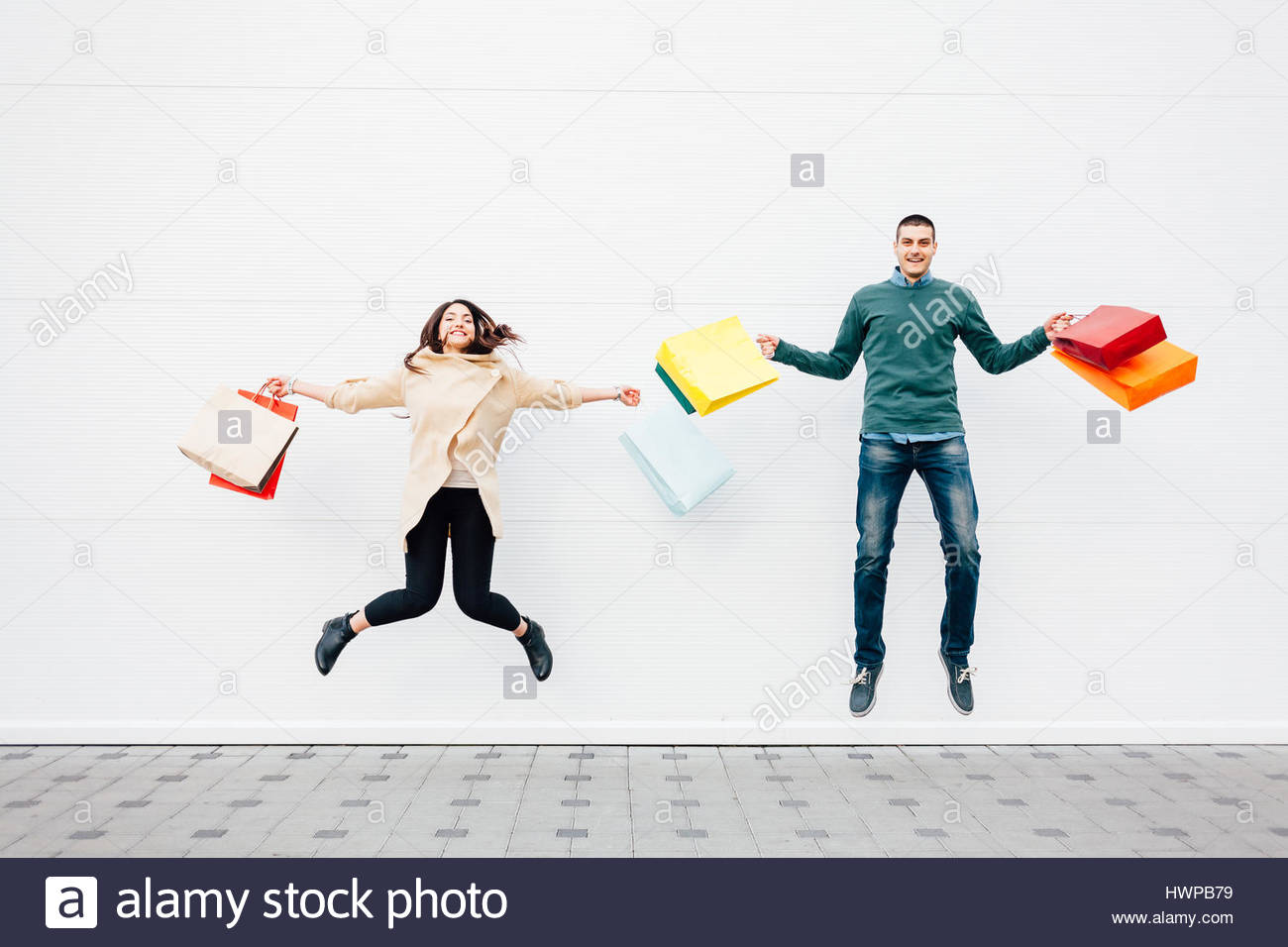 Excited young woman and man jumping with shopping bags - Stock Image