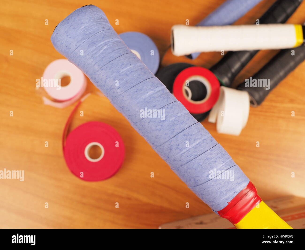 Freshly wrapped blue over grip on a Tennis racket providing a tacky surface for a firm grip, with grip work materials - Stock Image