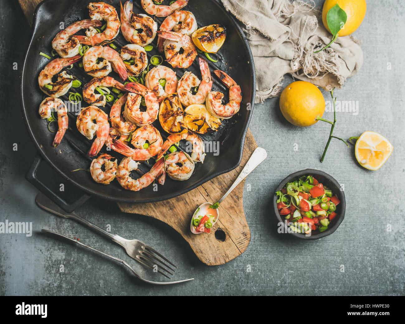 Grilled tiger prawns in pan with lemon, leek, chili, sauce - Stock Image