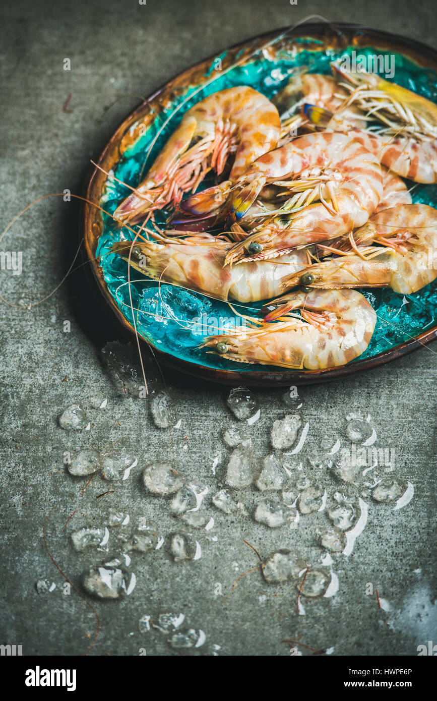 Raw uncooked tiger prawns on chipped ice in tray - Stock Image