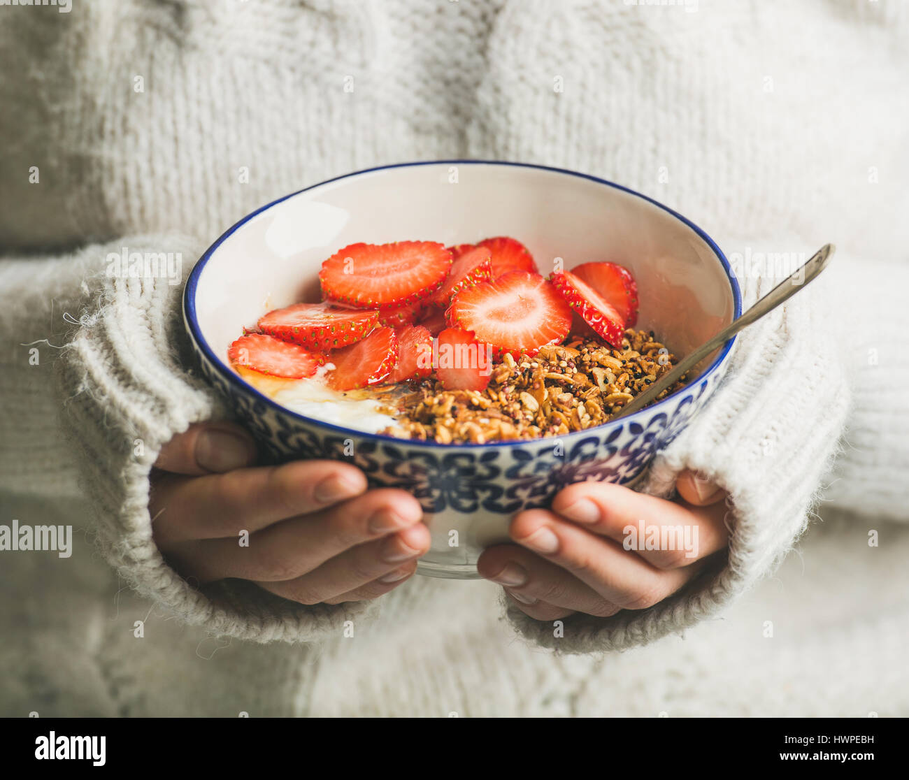 Healthy breakfast yogurt, granola, strawberry bowl in hands of woman - Stock Image