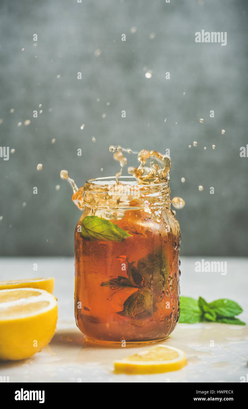 Iced tea with bergamot, lemon, mint in jar with splashes - Stock Image