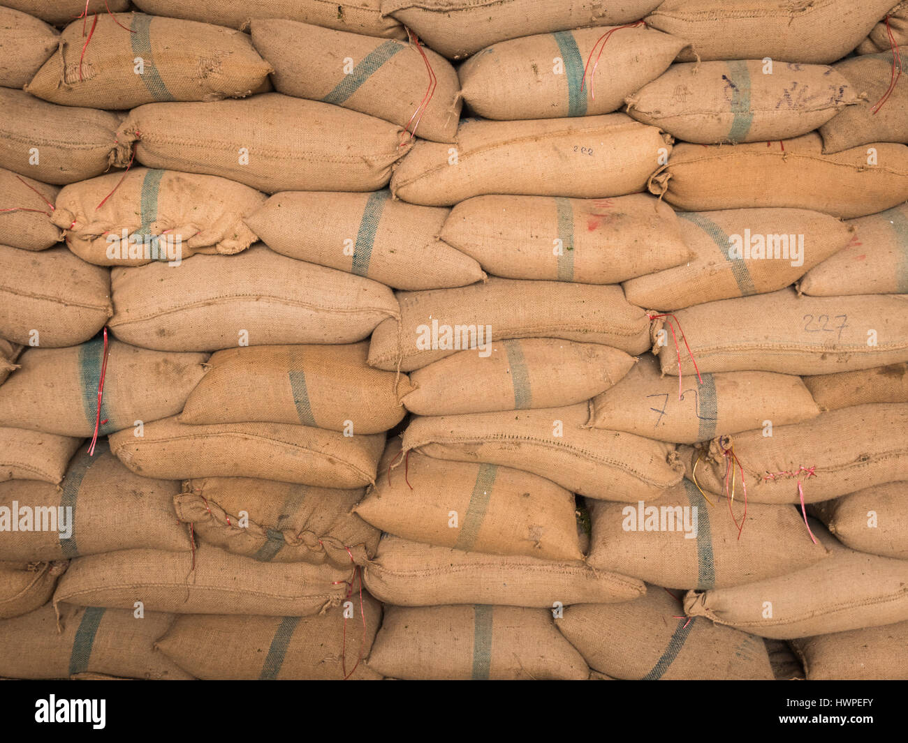 Old hemp sacks containing rice placed stacked in a row. Stock Photo