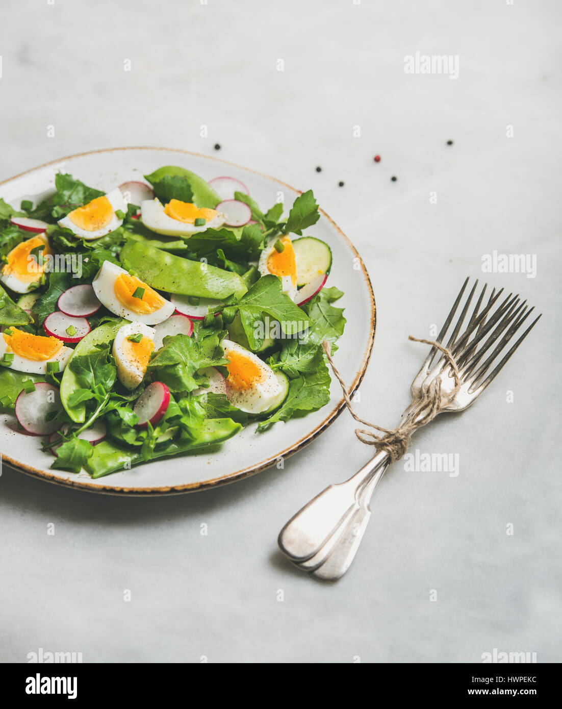 Healthy spring green salad with vegetables, pea and egg - Stock Image