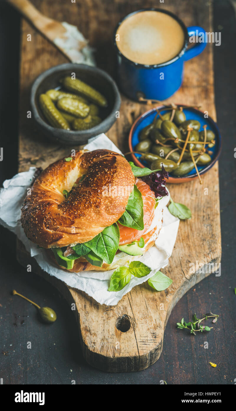Breakfast with salmon, avocado, cream-cheese, basil bagel, espresso coffee, capers - Stock Image