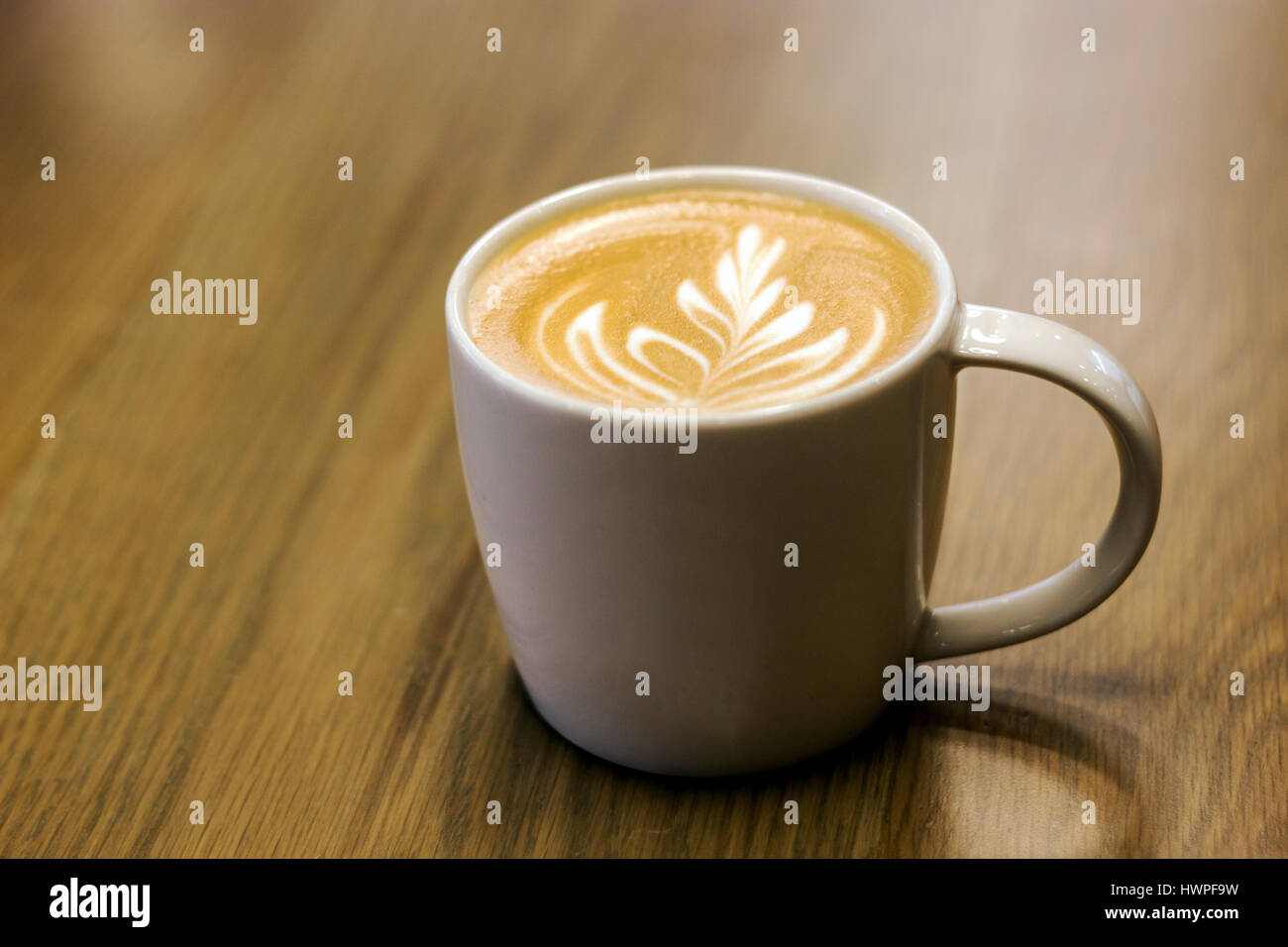 close up late art like fern on top of capucinno coffee on wood background in dark concept - Stock Image