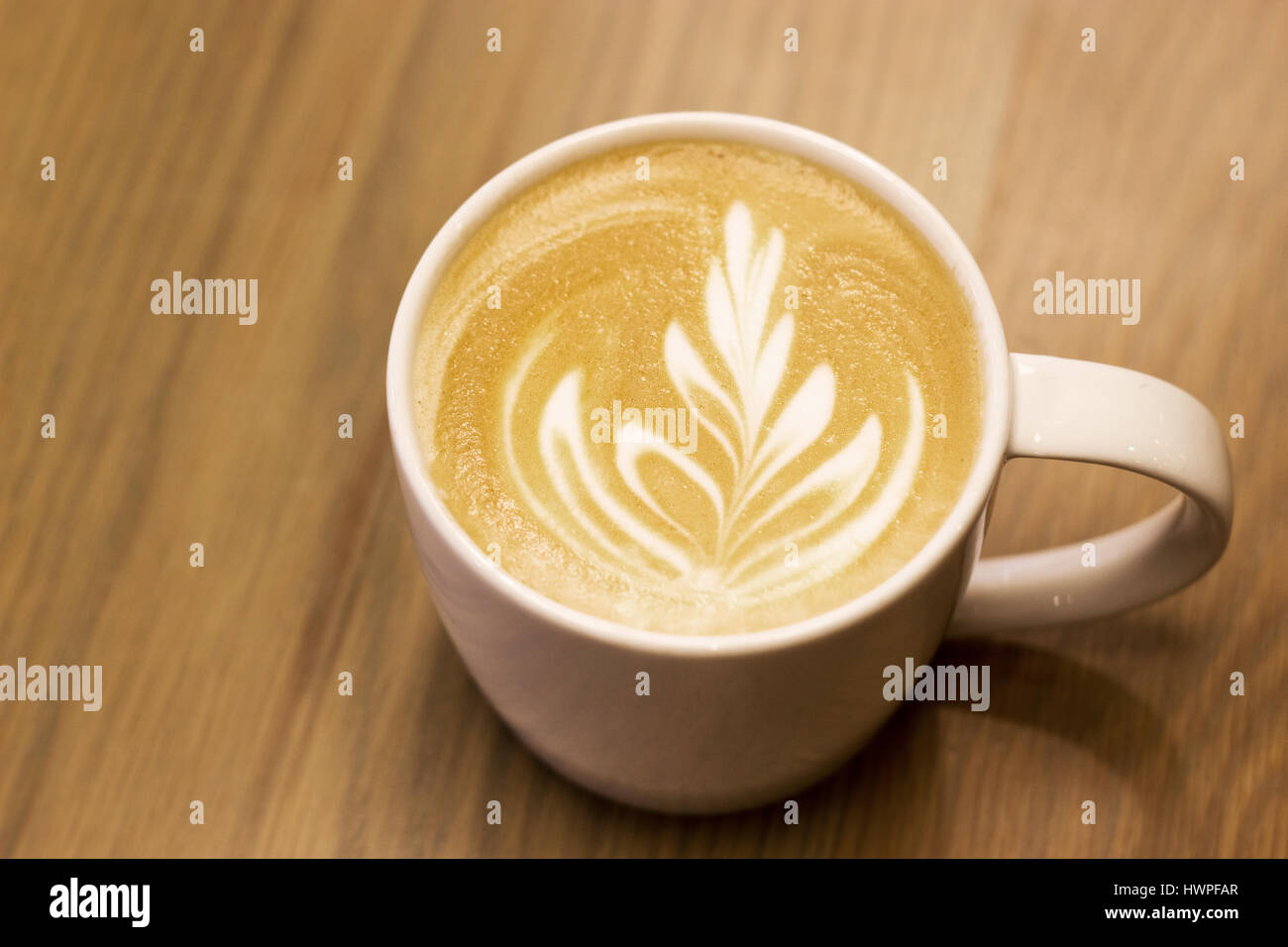 close up late art like fern on top of capucinno coffee on wood background - Stock Image