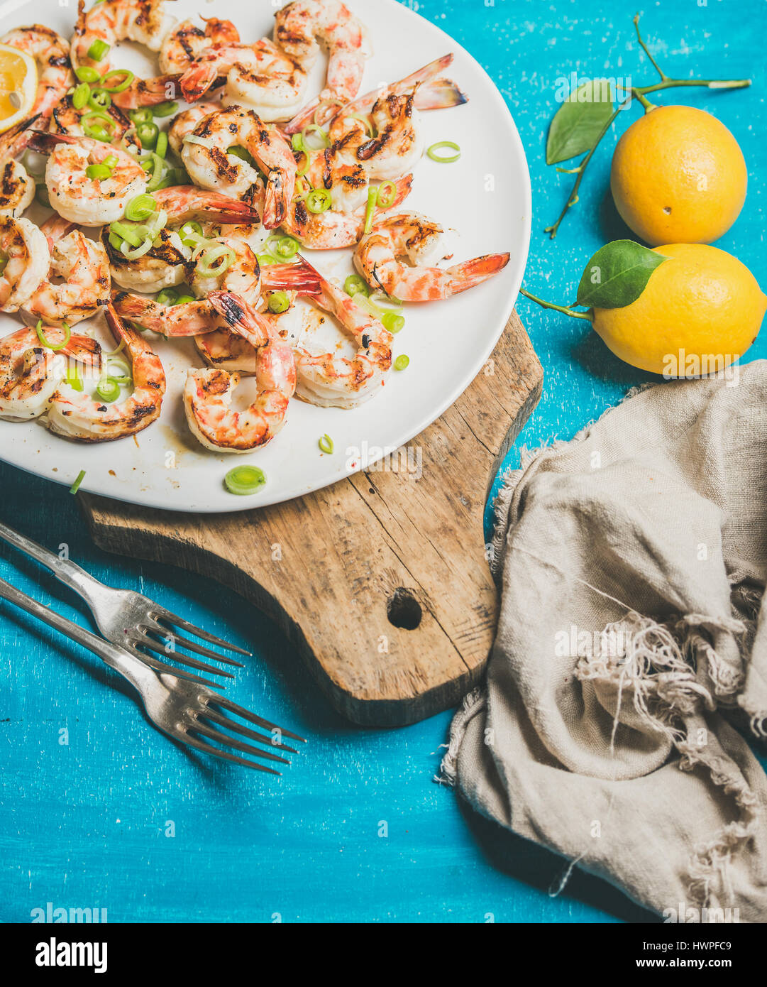 Grilled tiger prawns with lemon, leek and saucein white plate - Stock Image