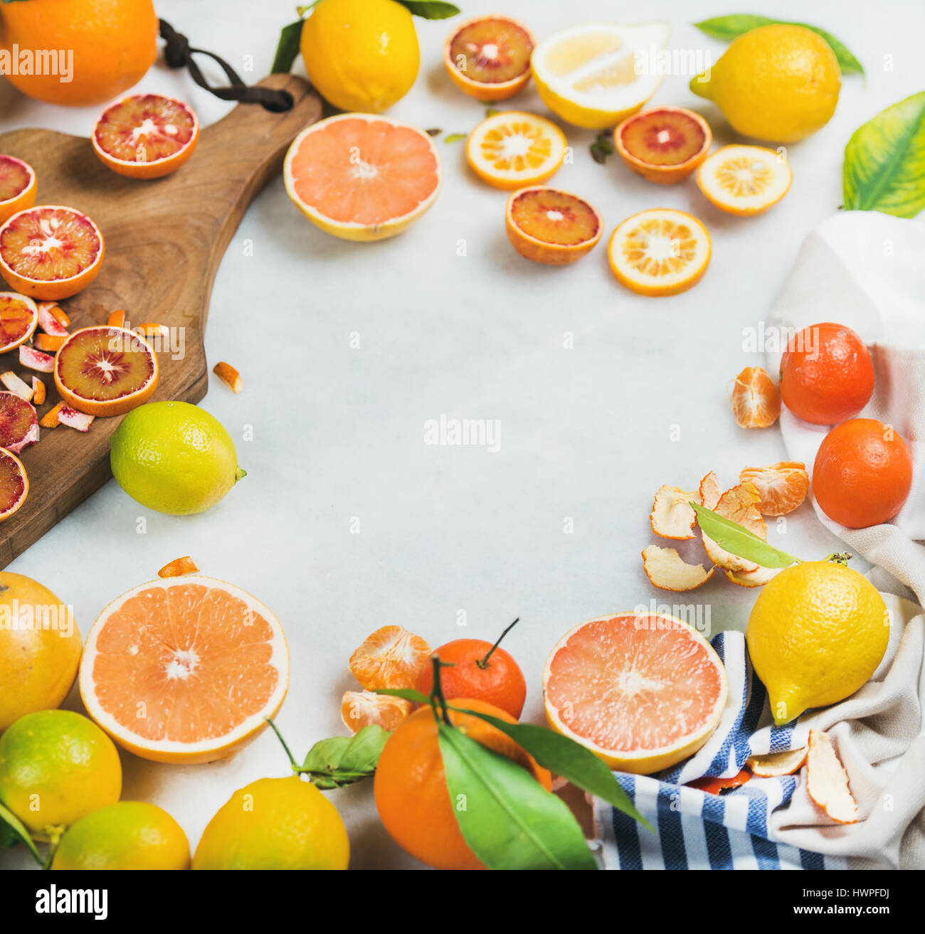 Citrus fruits slices on wooden board over grey marble background - Stock Image