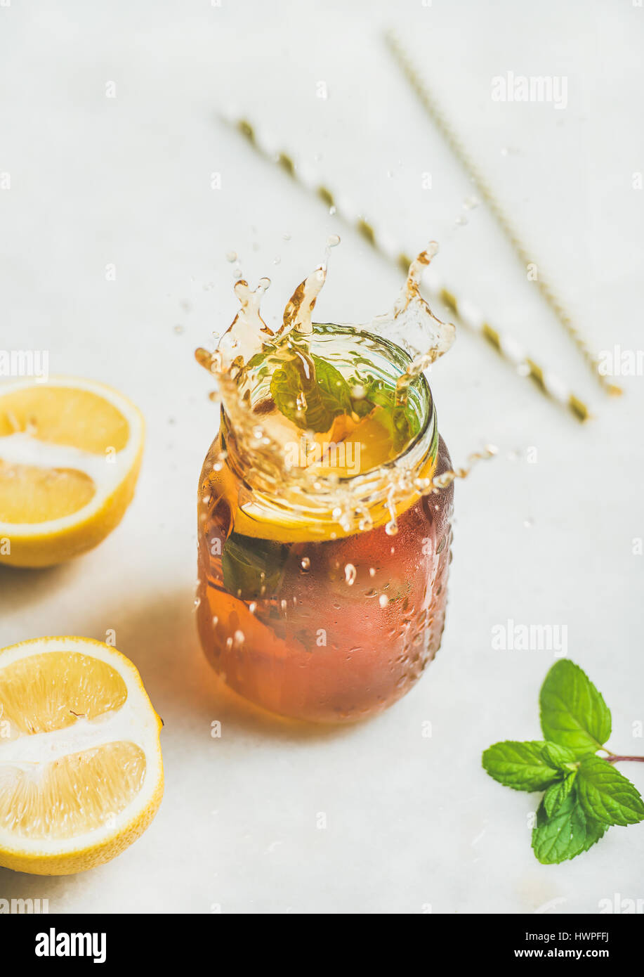 Summer cold Iced tea with lemon and herbs, vertical composition - Stock Image