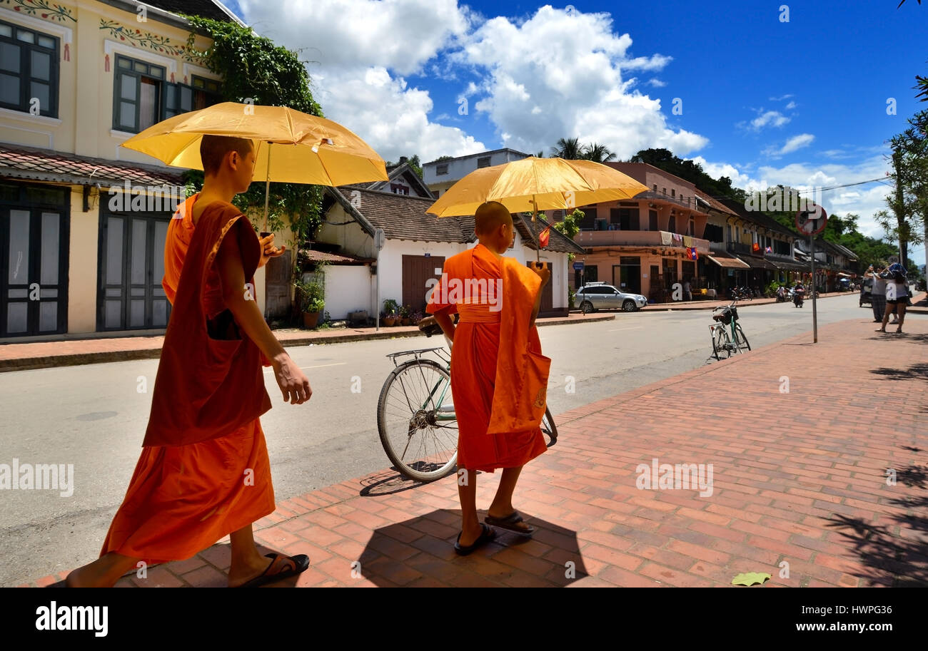 Loungprabang, Laos - August 7, 2015 : unidentified of 2 little monks are walking on the street with sun protect - Stock Image