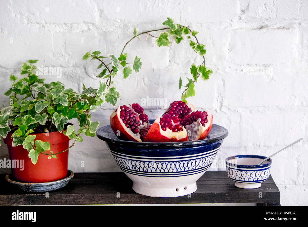 Close-up of pomegranate in plate on bowl by potted plant on table against brick wall - Stock Image