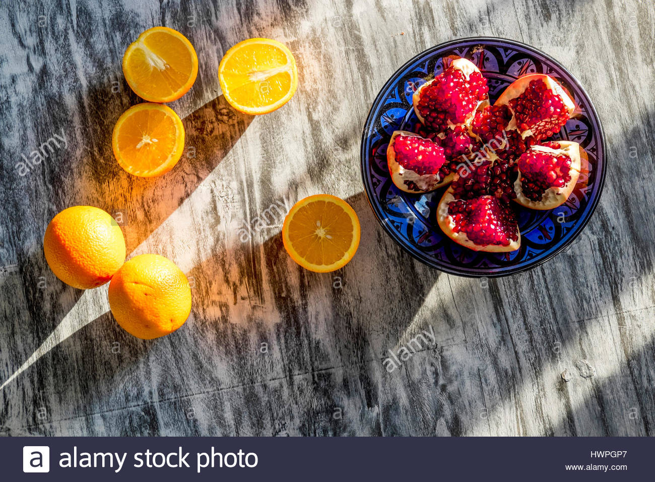 Overhead view of pomegranate and oranges on table - Stock Image