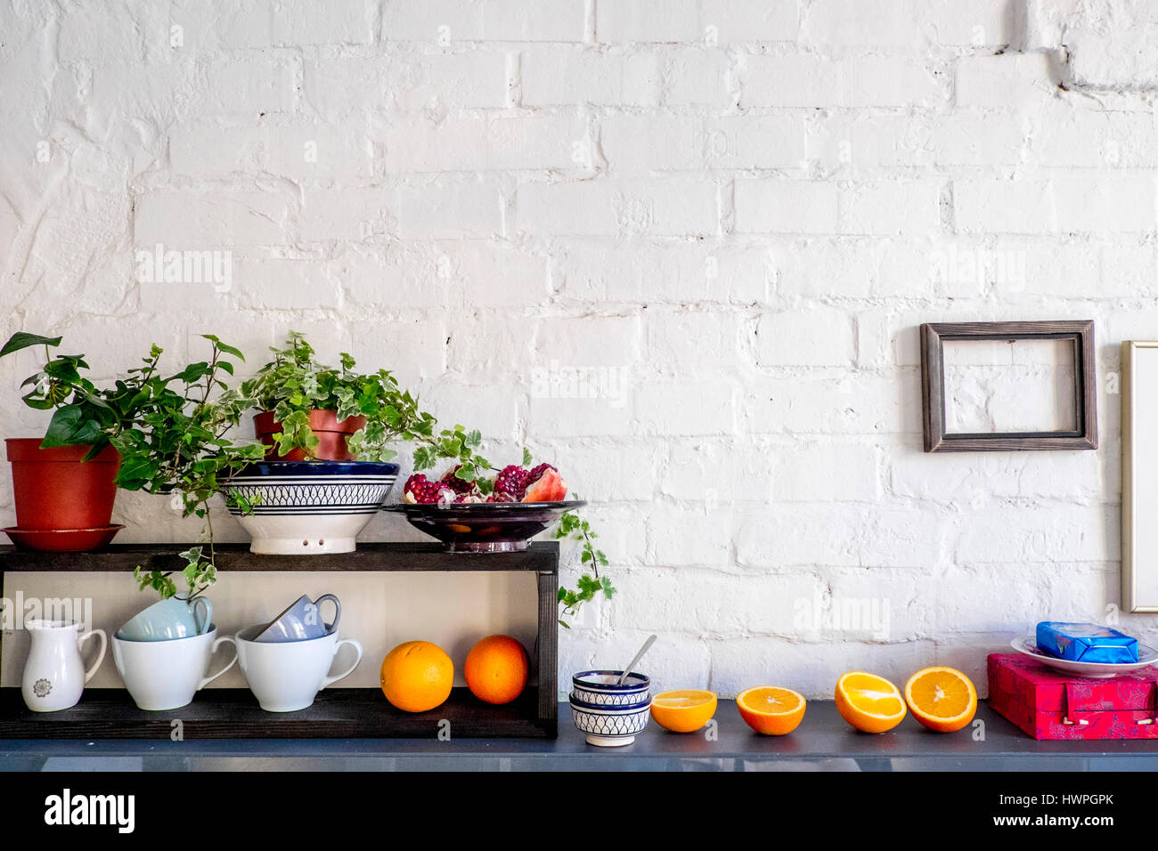 Potted plants and fruits with kitchen utensils on table against brick wall - Stock Image
