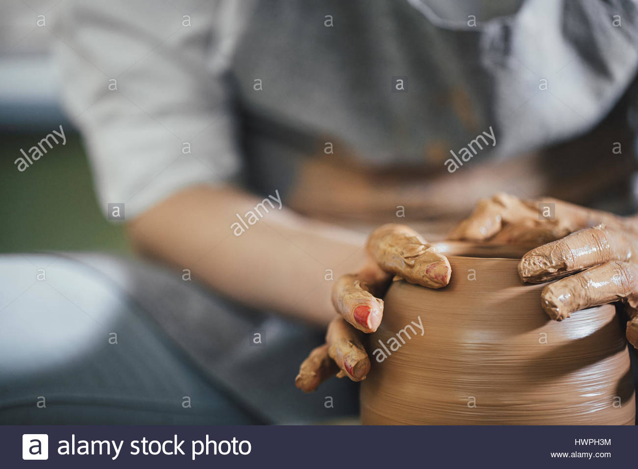Midsection of woman shaping clay on spinning wheel at workshop - Stock Image