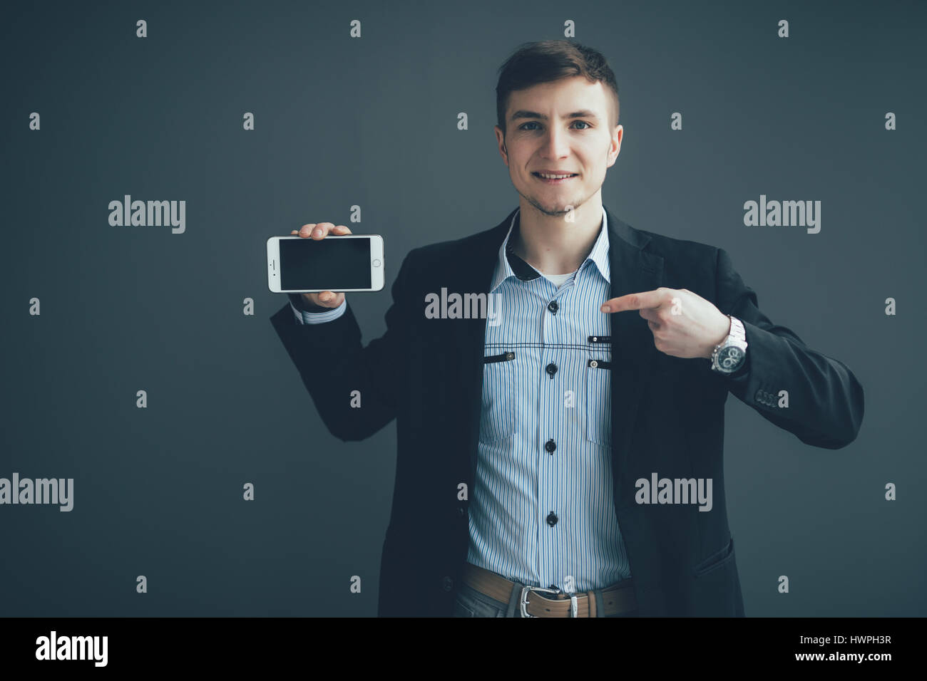 Businessman pointing finger on blank smartphone screen over black background - Stock Image