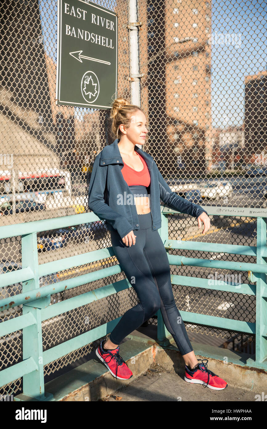 Female athlete standing by fence in city during sunny day - Stock Image