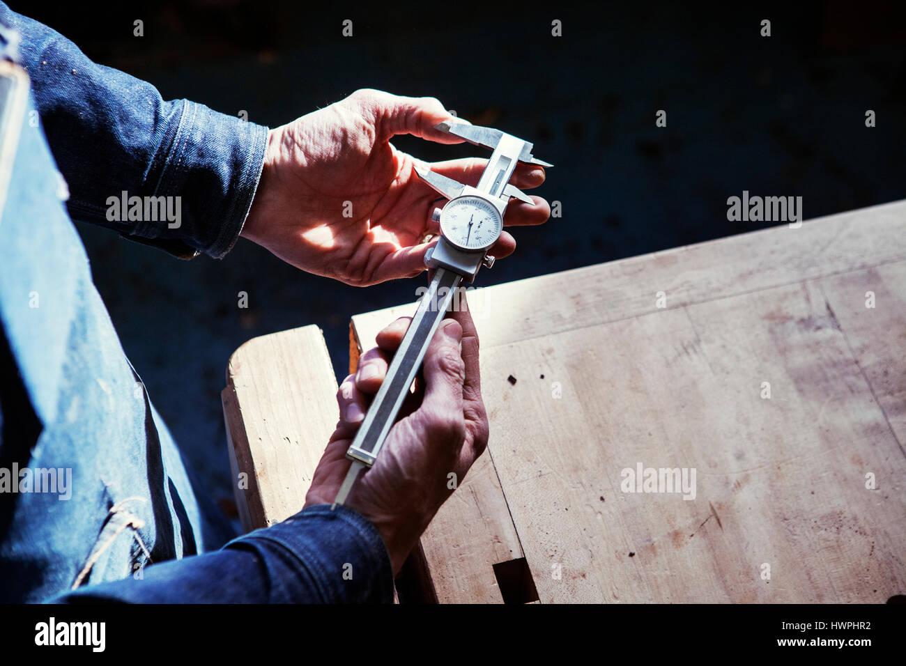 Midsection of carpenter holding vernier caliper at table in workshop - Stock Image