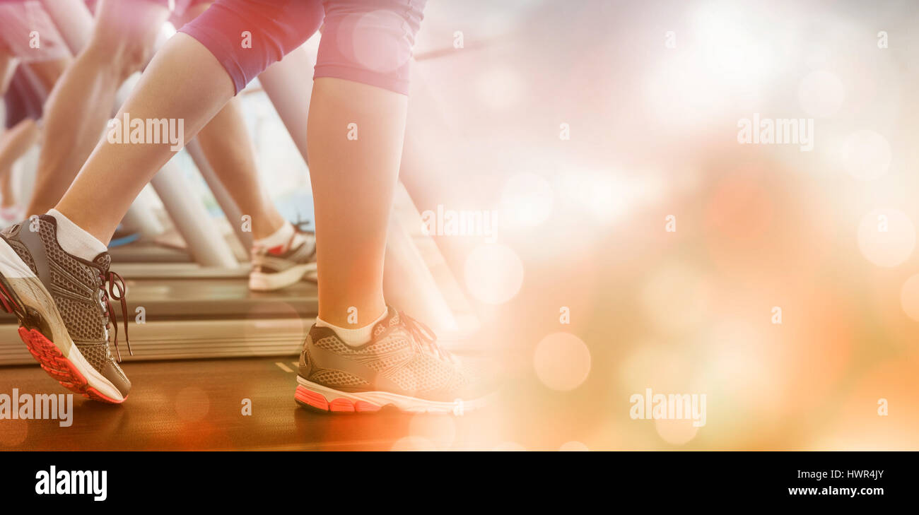 Row of people working out on treadmills at the gym - Stock Image