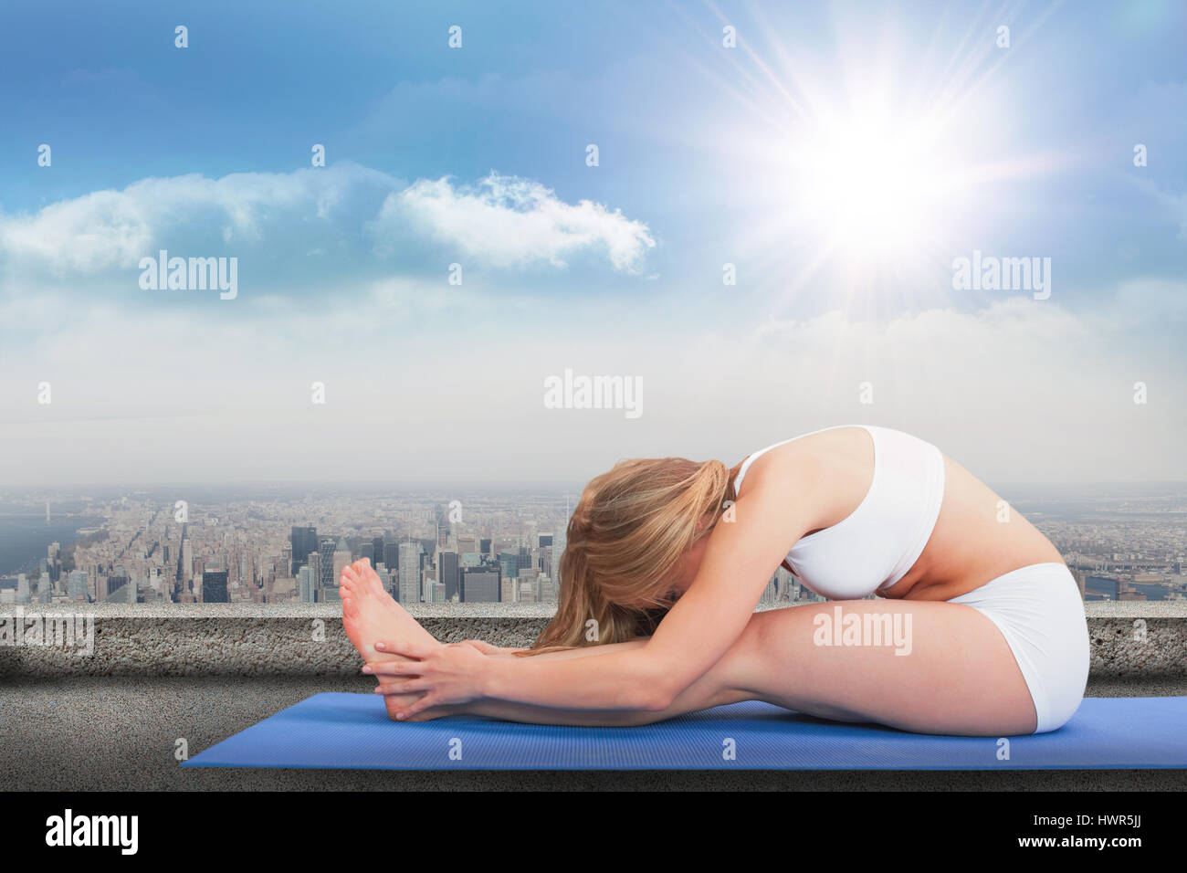 Side view of woman doing the paschimottanasana pose against balcony overlooking city - Stock Image