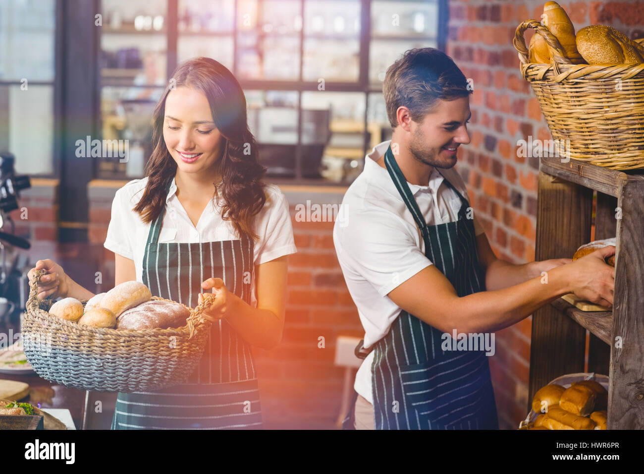 Graphic image of flare against happy co-workers working at coffee house - Stock Image