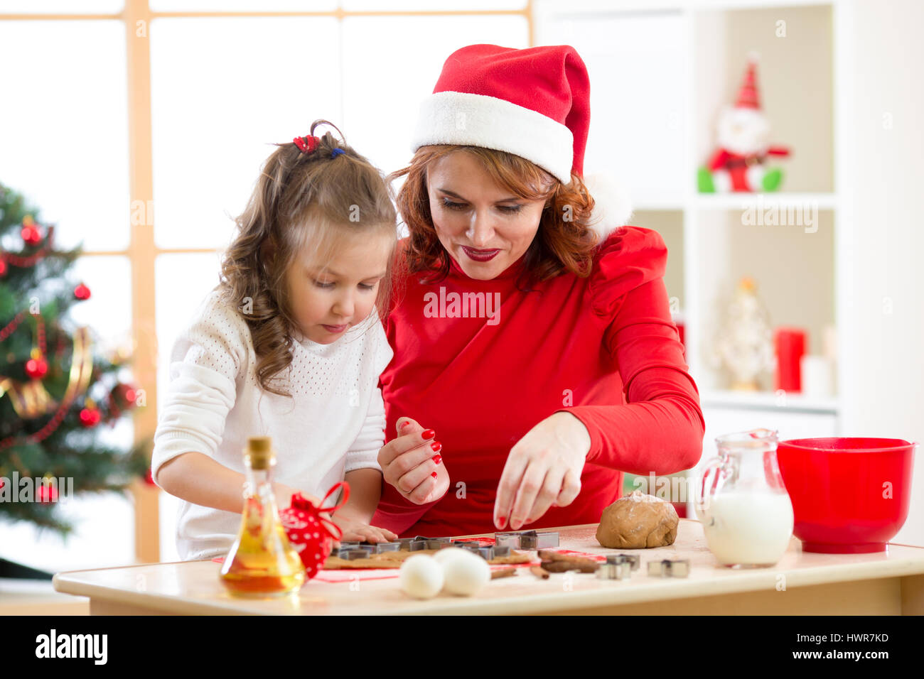 Happy kid girl and mother baking x-mas cookies together at festive decorated room - Stock Image