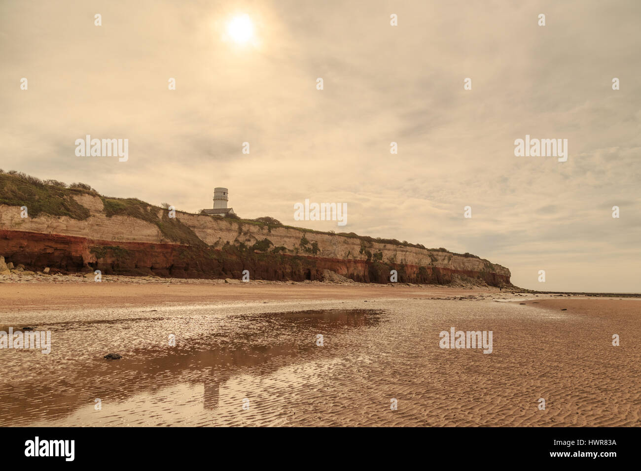 HUNSTANTON, ENGLAND - MARCH 10: Old Hunstanton Lighthouse (now a residence) reflected in rock pool on beach. HDR - Stock Image