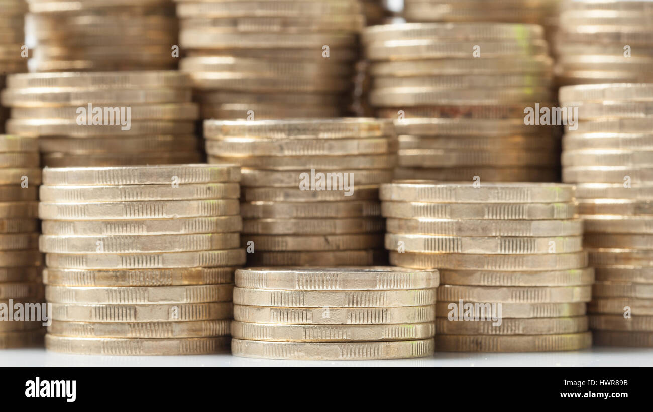 Many coins stacks piles arranged next to one another as background. - Stock Image