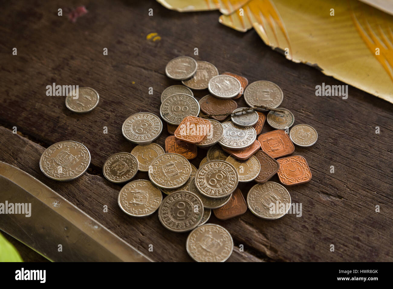 Surinamese coins on the counter top in a roadside market in Paramaribo, Suriname. - Stock Image