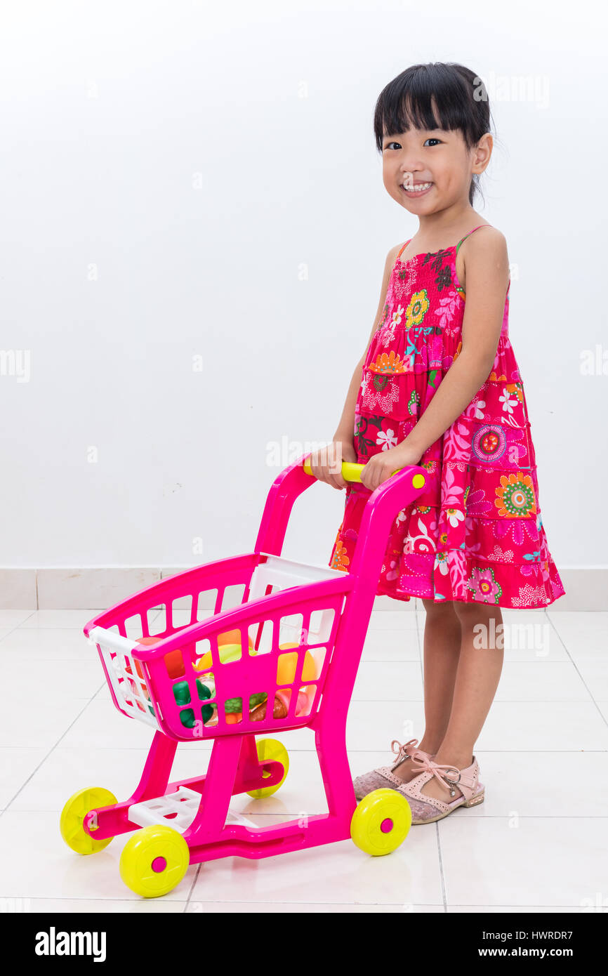 1e1a24bd2b4f Happy Asian Chinese little girl pushing toy trolley in isolated ...