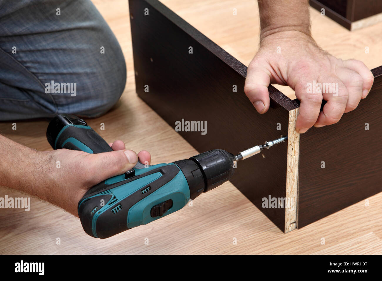 Assembling furniture from chipboard, Woodworker  screwing Chipboard screws using a cordless screwdriver. - Stock Image