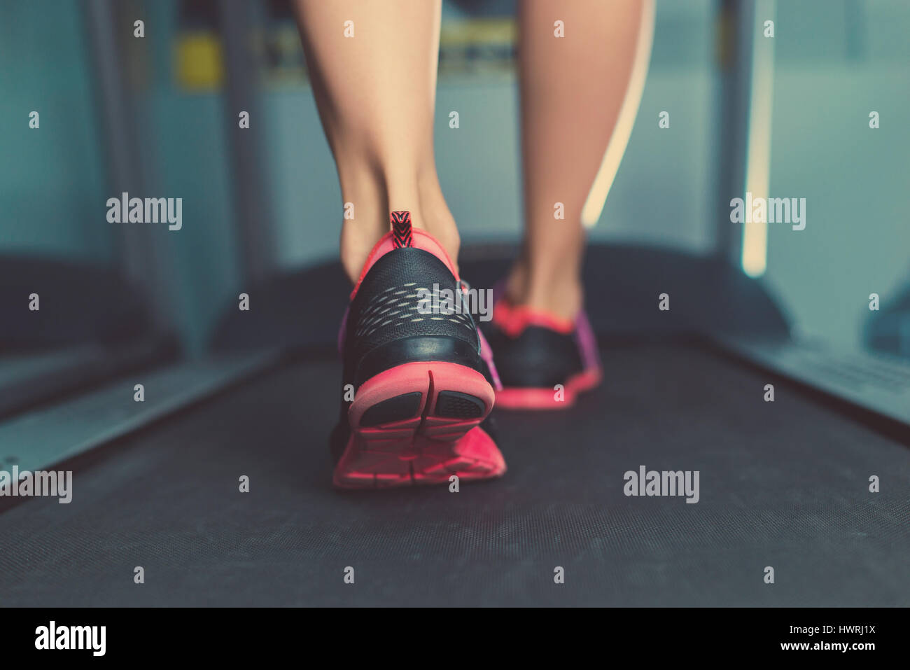 Female muscular feet in sneakers running on the treadmill at the gym. Concept for fitness, exercising and healthy - Stock Image