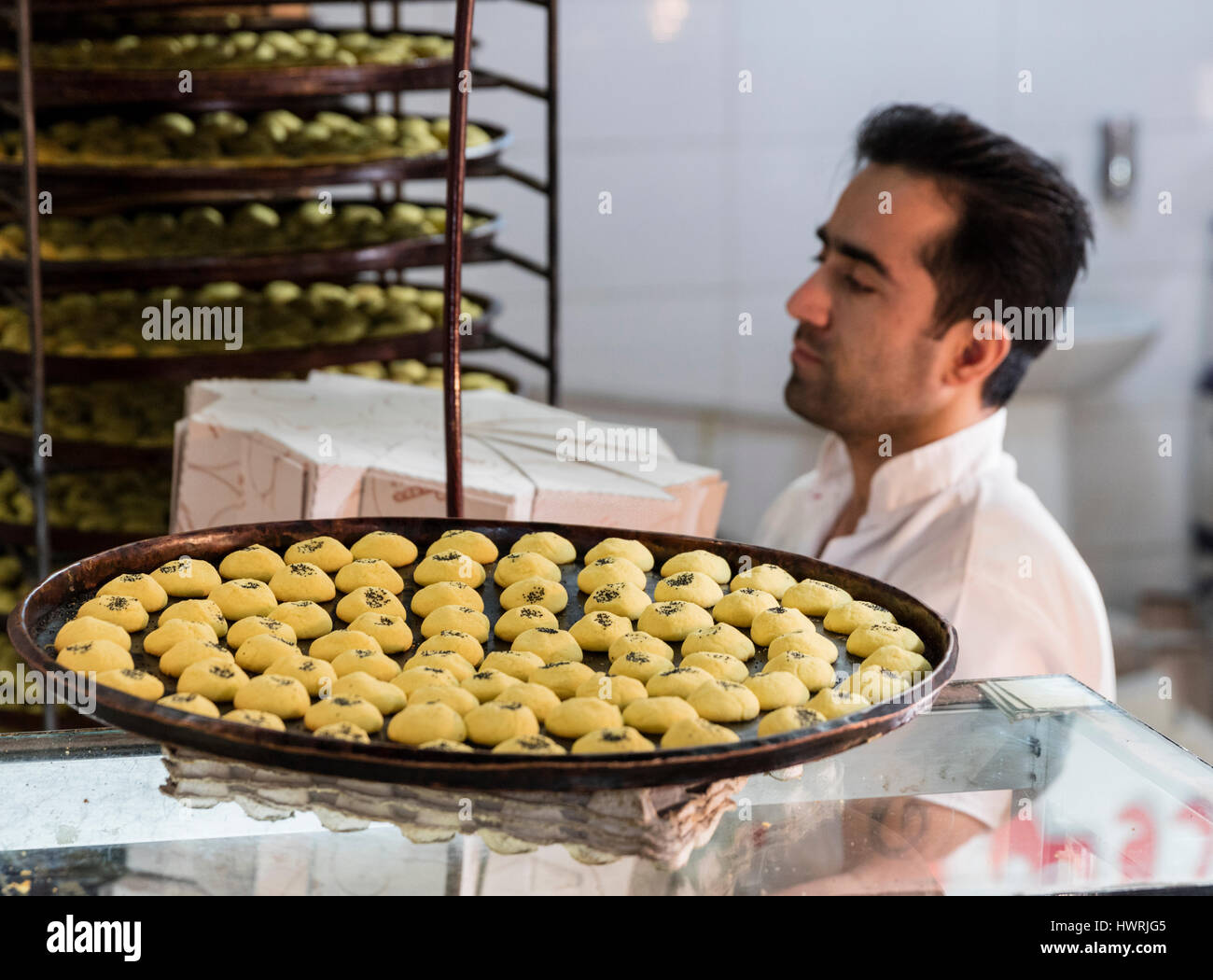 Baker and trays of chick pea flour cookies in the Kermanshah Bazaar. Serving these cookies at Norooz, the Persian - Stock Image