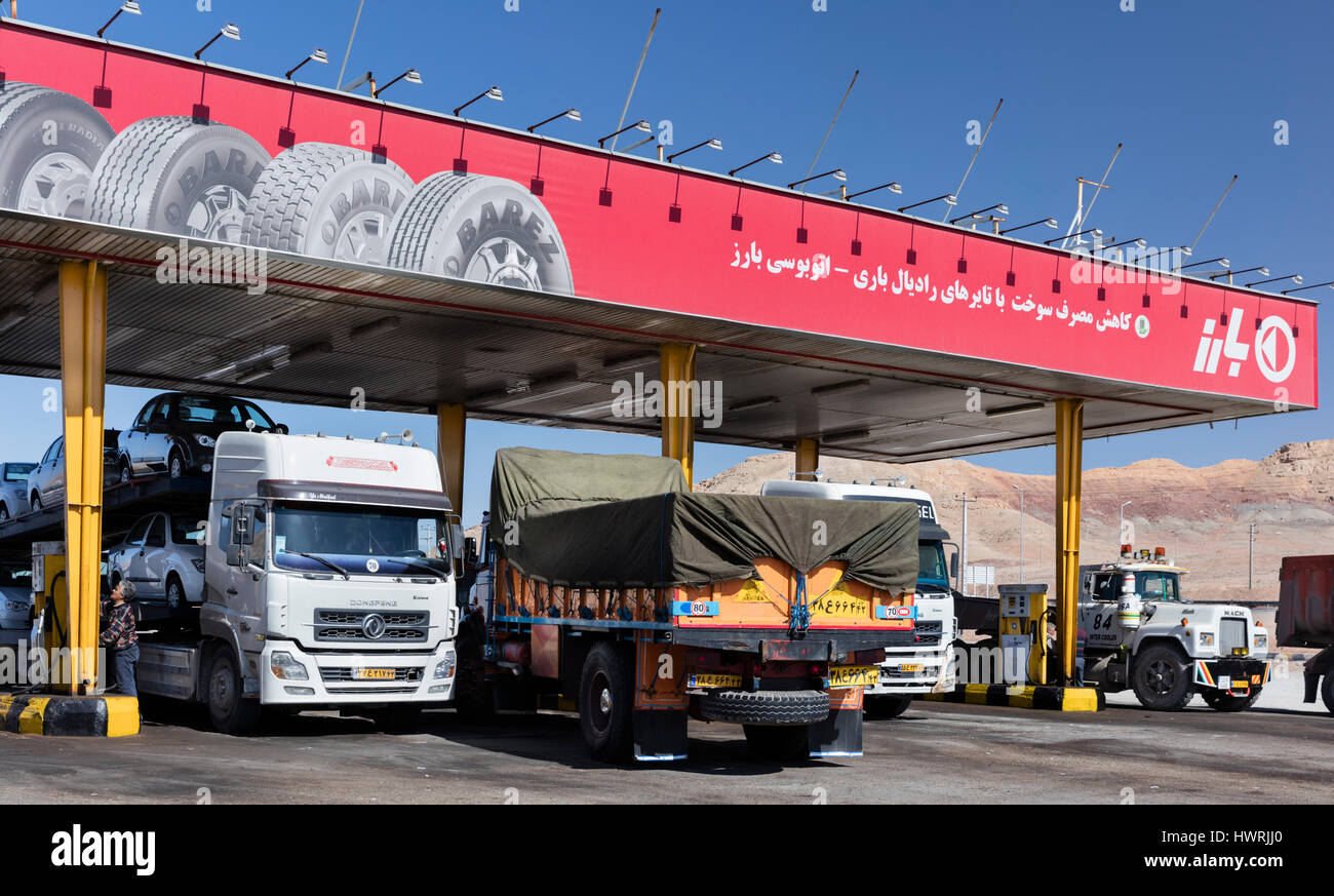 Heavy trucks at Iranian gasoline station on the road to Isfahan. One driver is at a gasoline pump - Stock Image