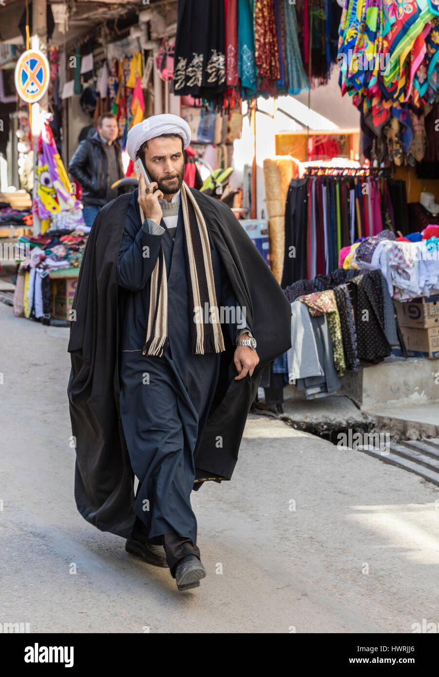 White-turbaned mullah striding through the bazaar at Khorramabad while talking on cellphone - Stock Image