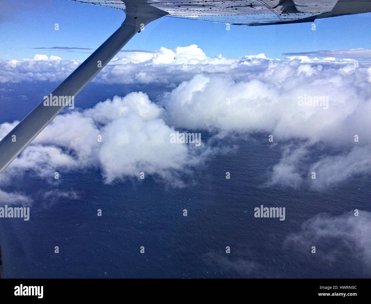 View from window of a light plane flying above the clouds over the ocean. Stock Photo