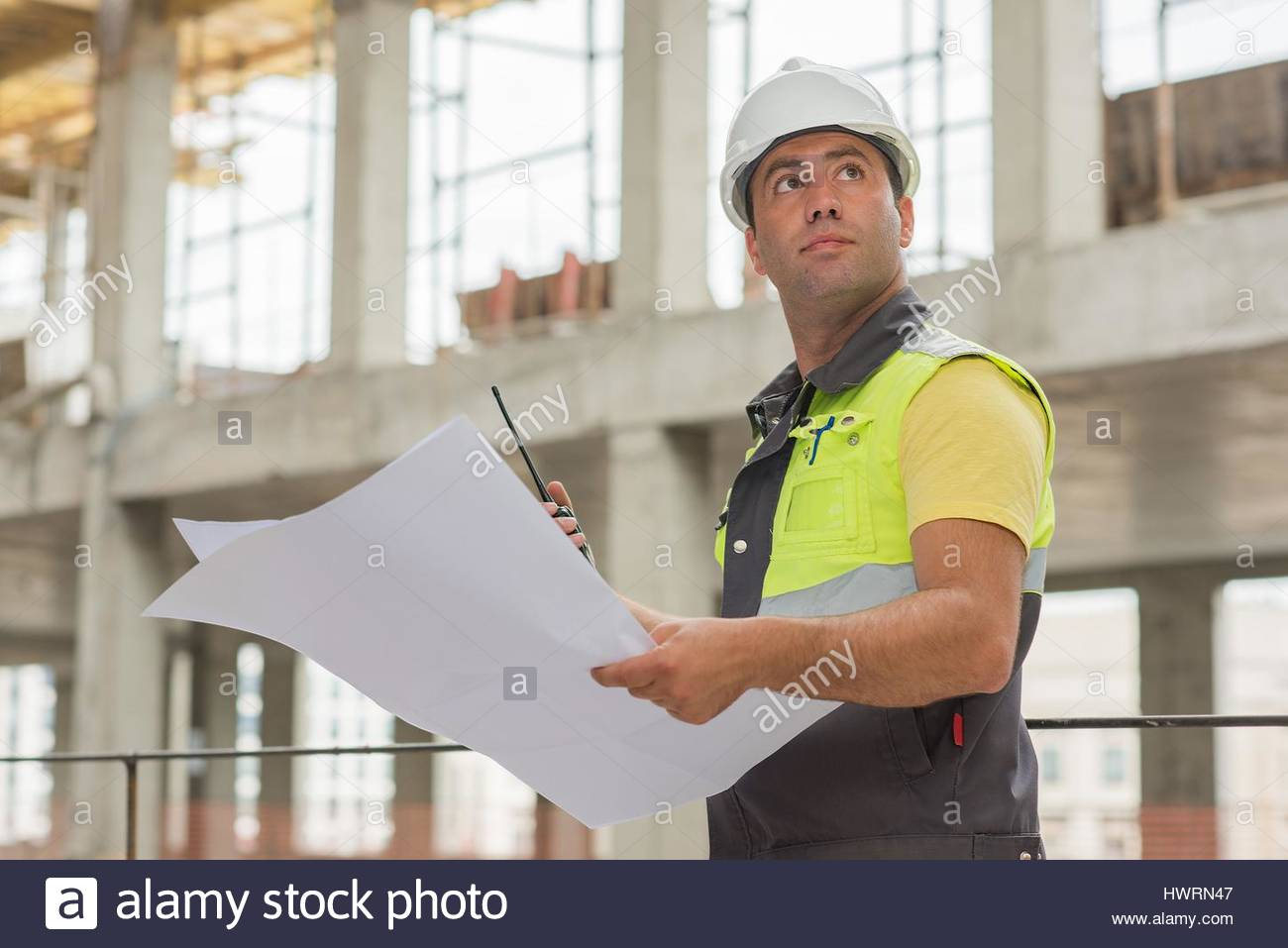 Civil Engineer at construction site is inspecting ongoing production according to design drawings. - Stock Image