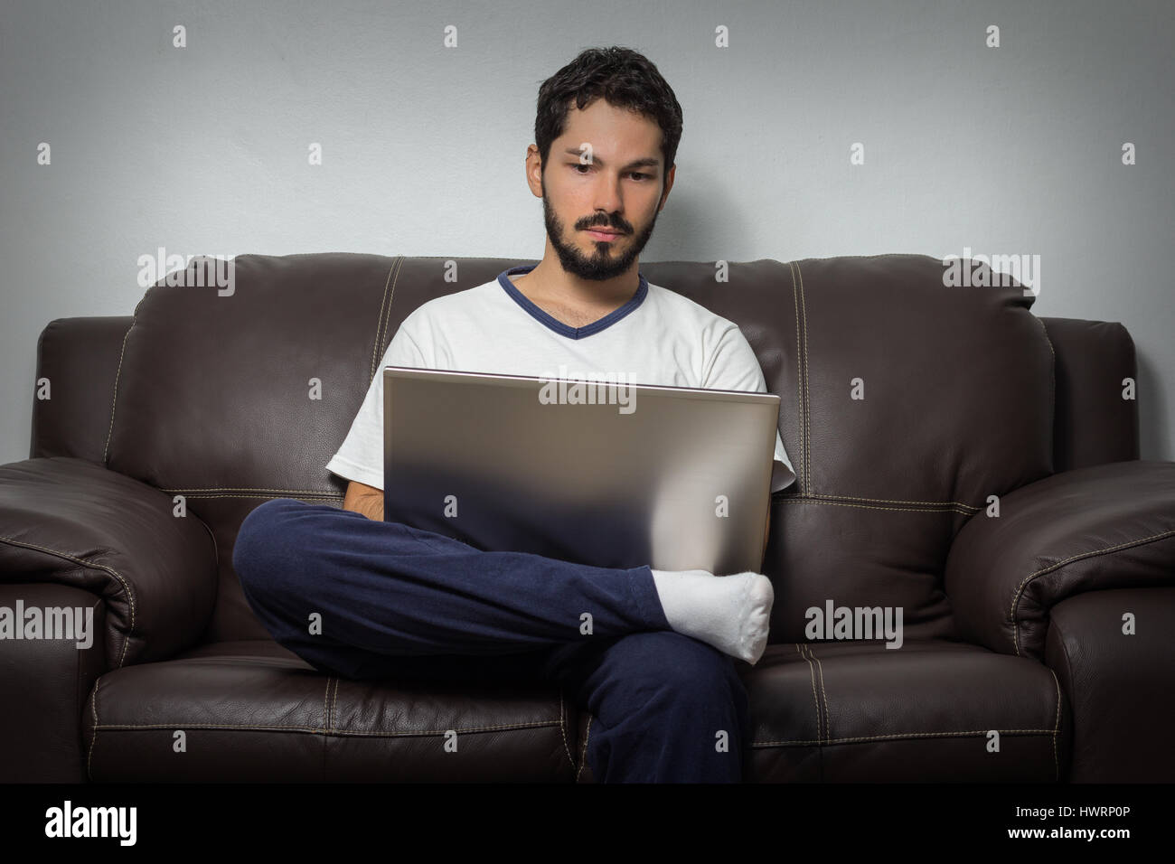 Serious worker at his home office working working with a laptop in the lap. - Stock Image