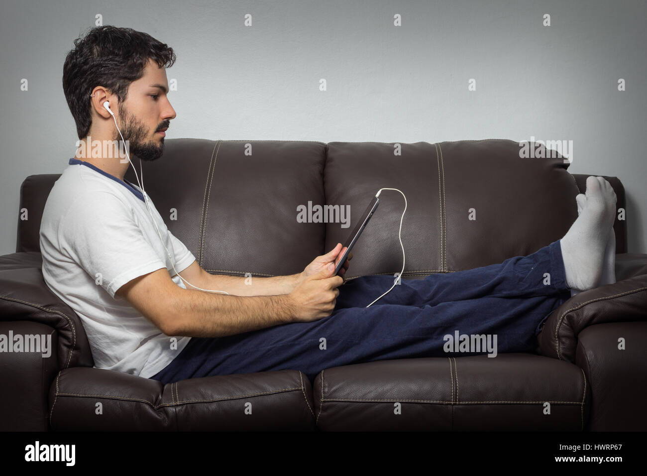 Attractive young man listening to music and browsing the internet with digital tablet on couch. Indoors - Stock Image