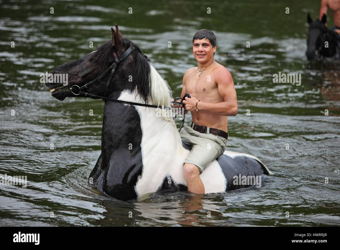 Young man astride horse go down the river - Stock Image