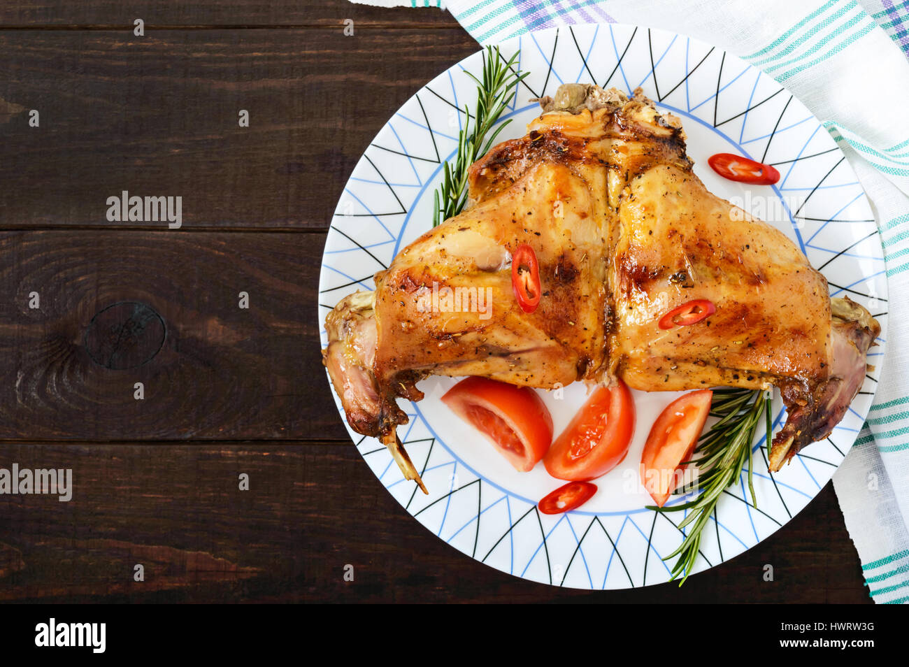 Baked rabbit legs on a plate on a dark wooden background. Dietary menu. Top view. - Stock Image
