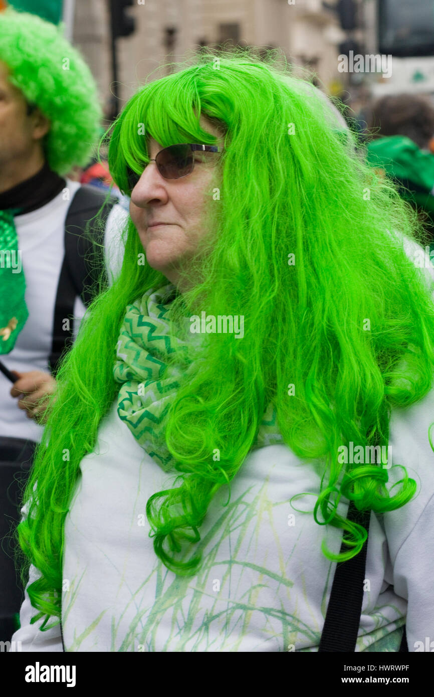 Woman wearing a green wig for the St Patricks day parade London - Stock Image