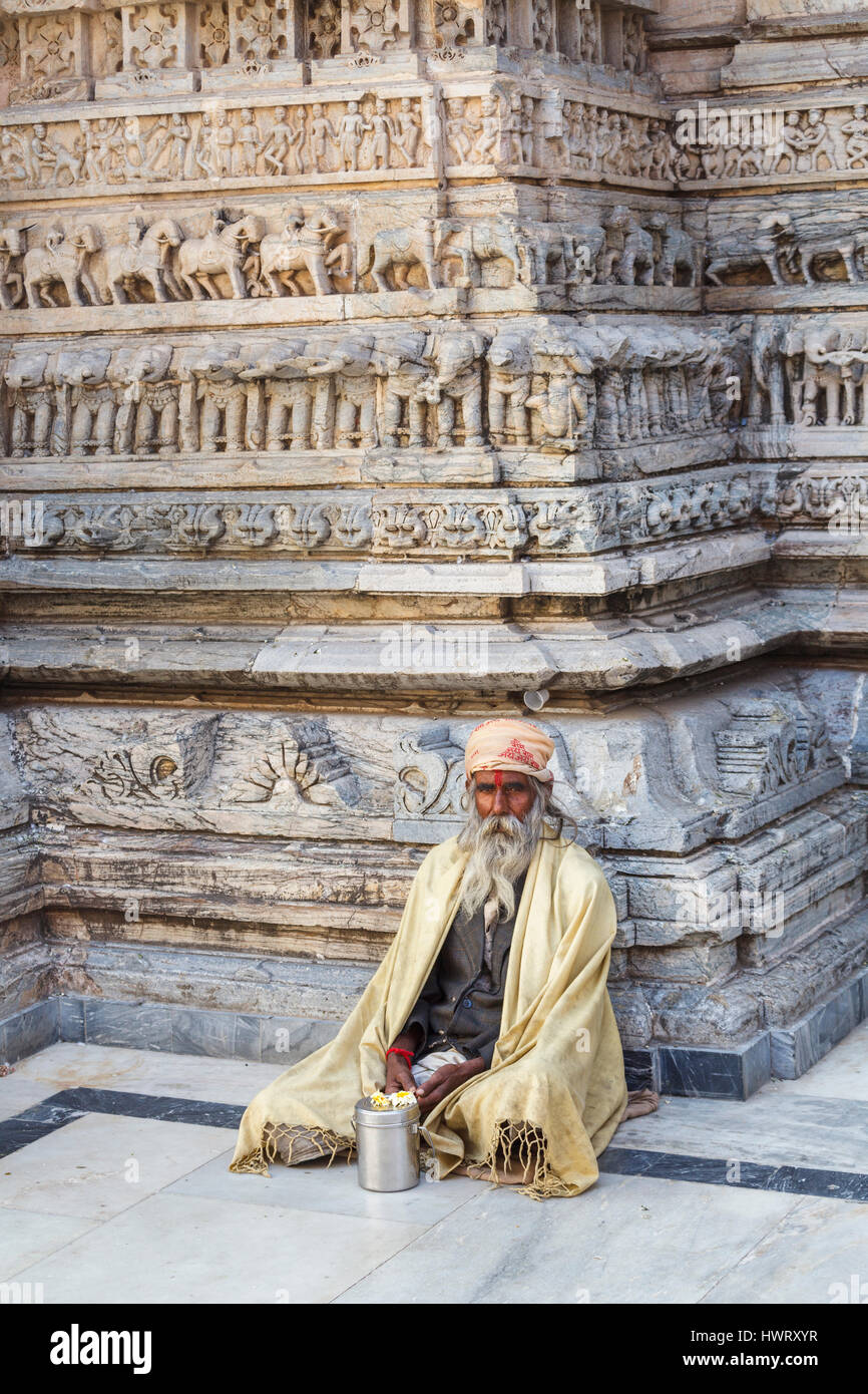 Sadhu sitting cross-legged by a typical carved wall in the Jagdish Temple, a Hindu temple in Udaipur, Indian state - Stock Image