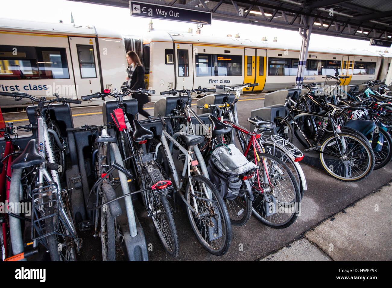Tonbridge,Kent,UK.Cycles racked at Tonbridge railway station, Kent, UK, as a Southeastern railways train stands - Stock Image
