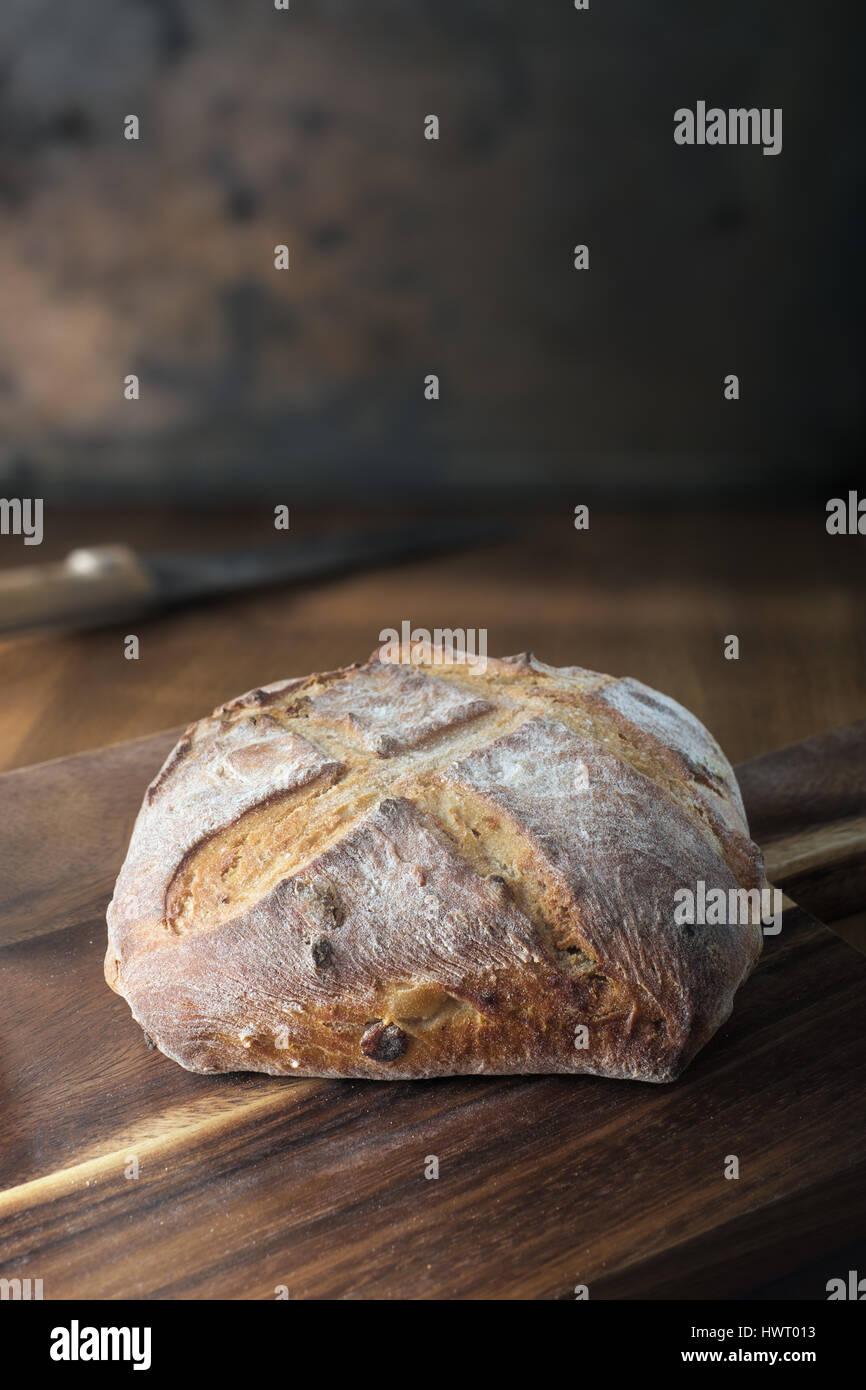 Rustic bread on cutting board - Stock Image