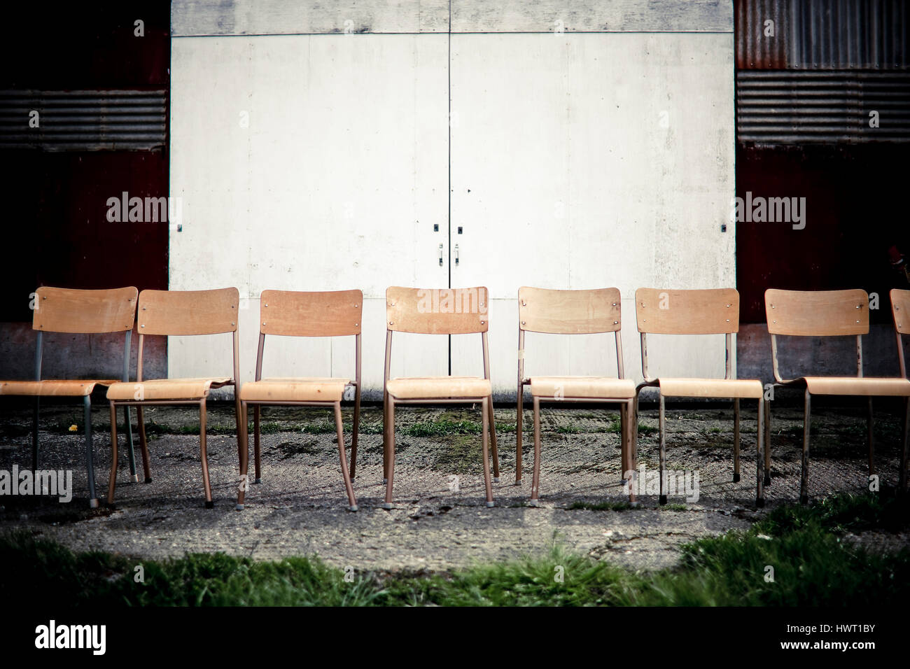 Empty chairs on footpath against closed door Stock Photo