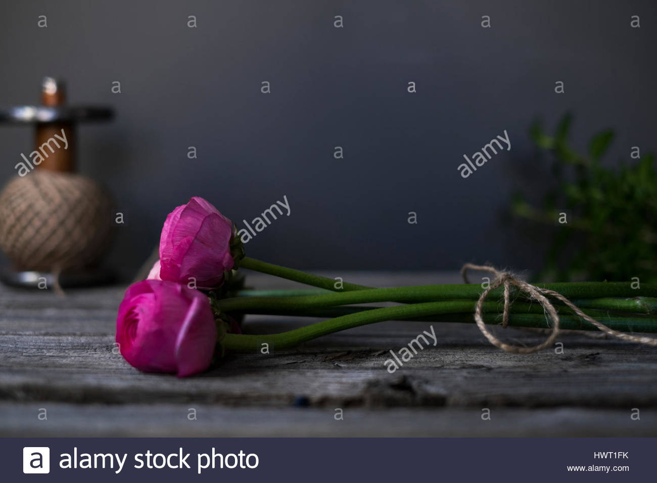 Close-up of pink roses and spool on wooden table - Stock Image