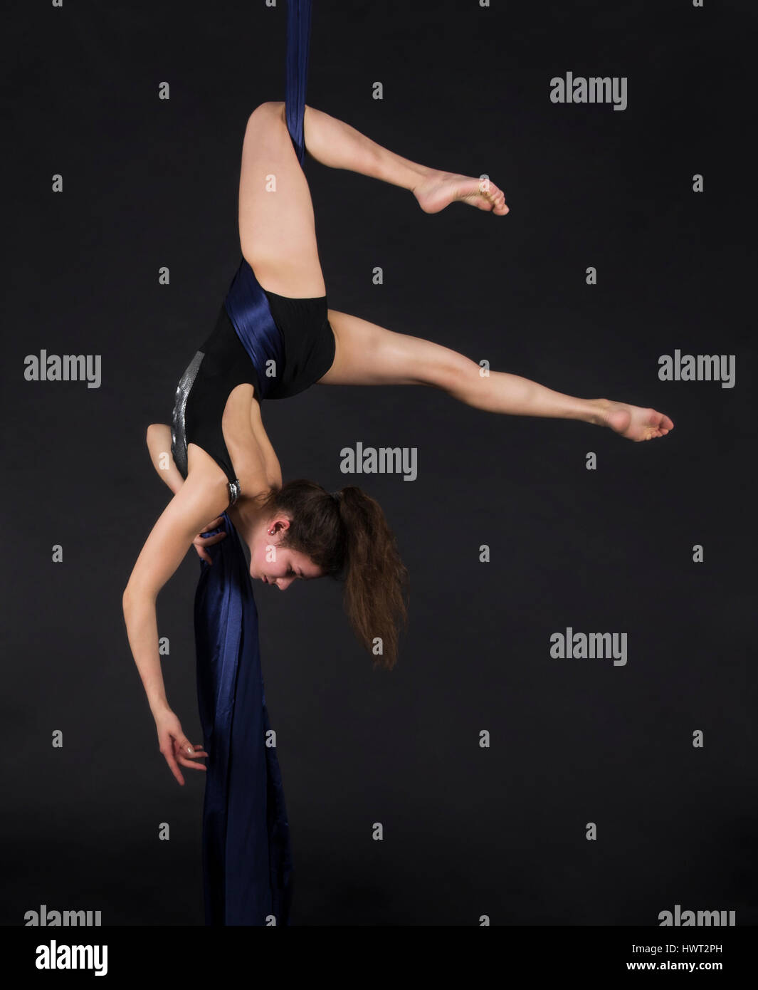 Young,smiling girl does exercises on the canvases. Studio recording of the performance on a dark background. - Stock Image