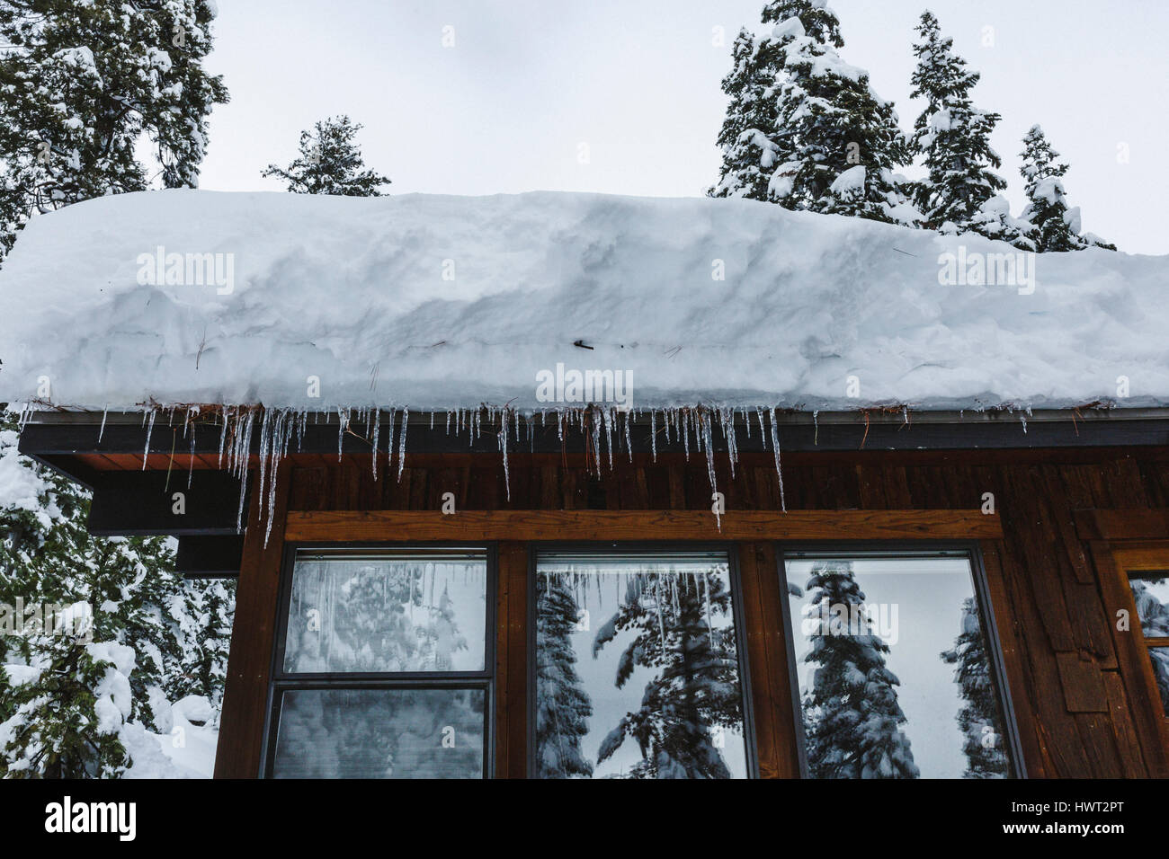 Low angle view of snow on house roof with icicles - Stock Image